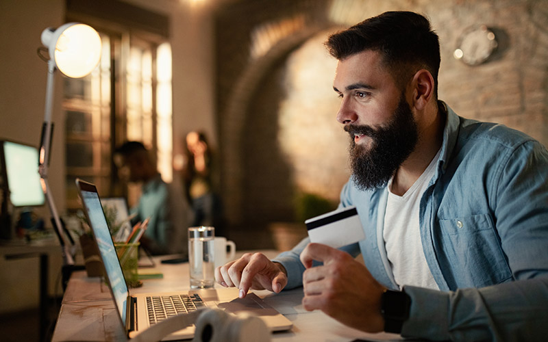 Man with beard making online payment through his card on a laptop